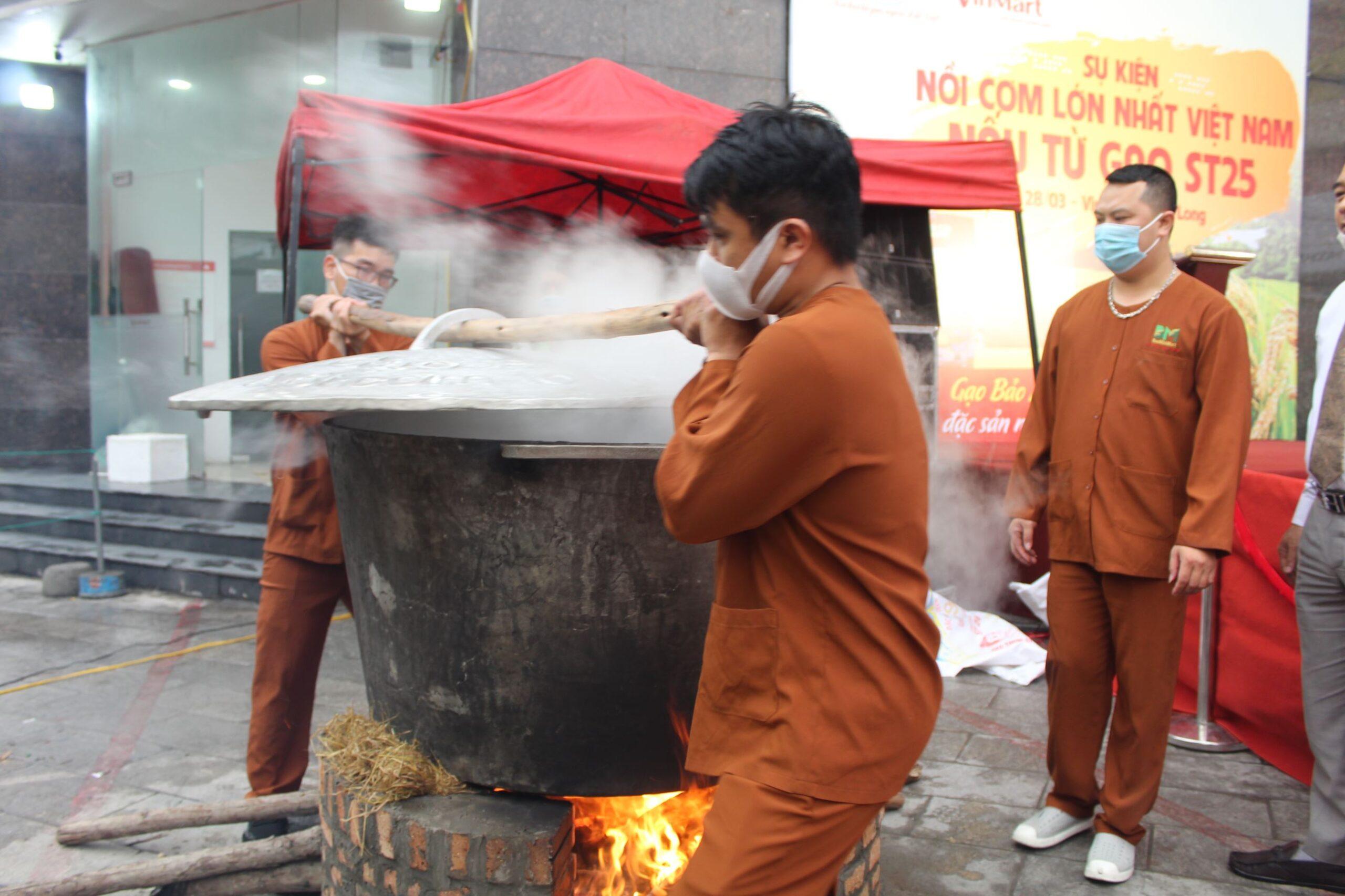 Nhân viên phụ trách nấu cơm cùng nhau hợp sức khiêng nắp vung để chuẩn bị đổ gạo vào nước đang sôi trong nồi.