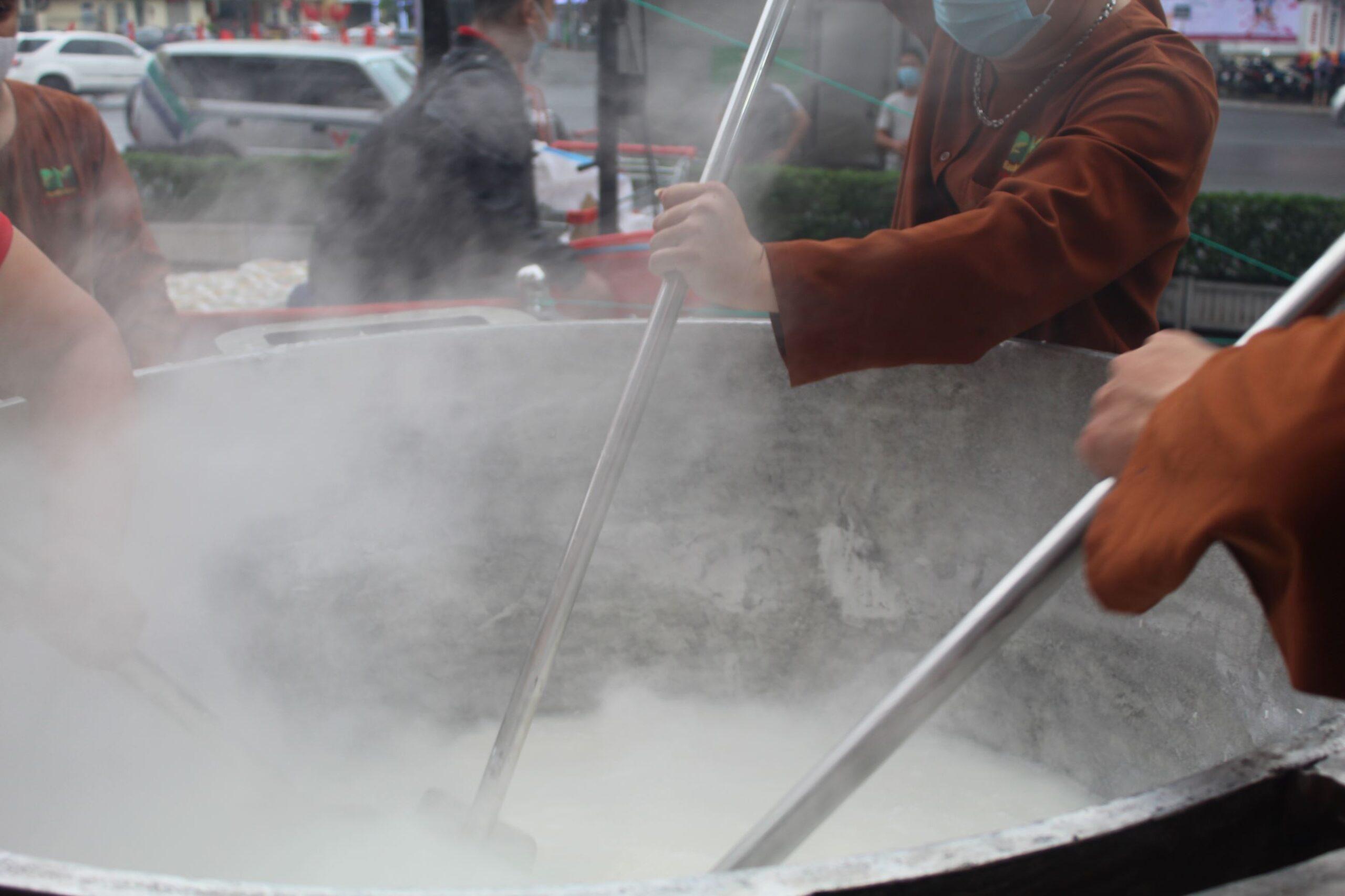 Nhân viên Bảo Minh cùng nhau dùng những chiếc muôi khổng lồ khuấy đảo để xôi được chín đều. Phương pháp nấu cơm truyền thống bằng bếp củi đòi hỏi kỹ thuật điêu luyện và kinh nghiệm từ người đứng bếp. Nhưng cơm khi nấu xongsẽ ngon hơn khi nấu bằng những thiết bị máy hiện đại.