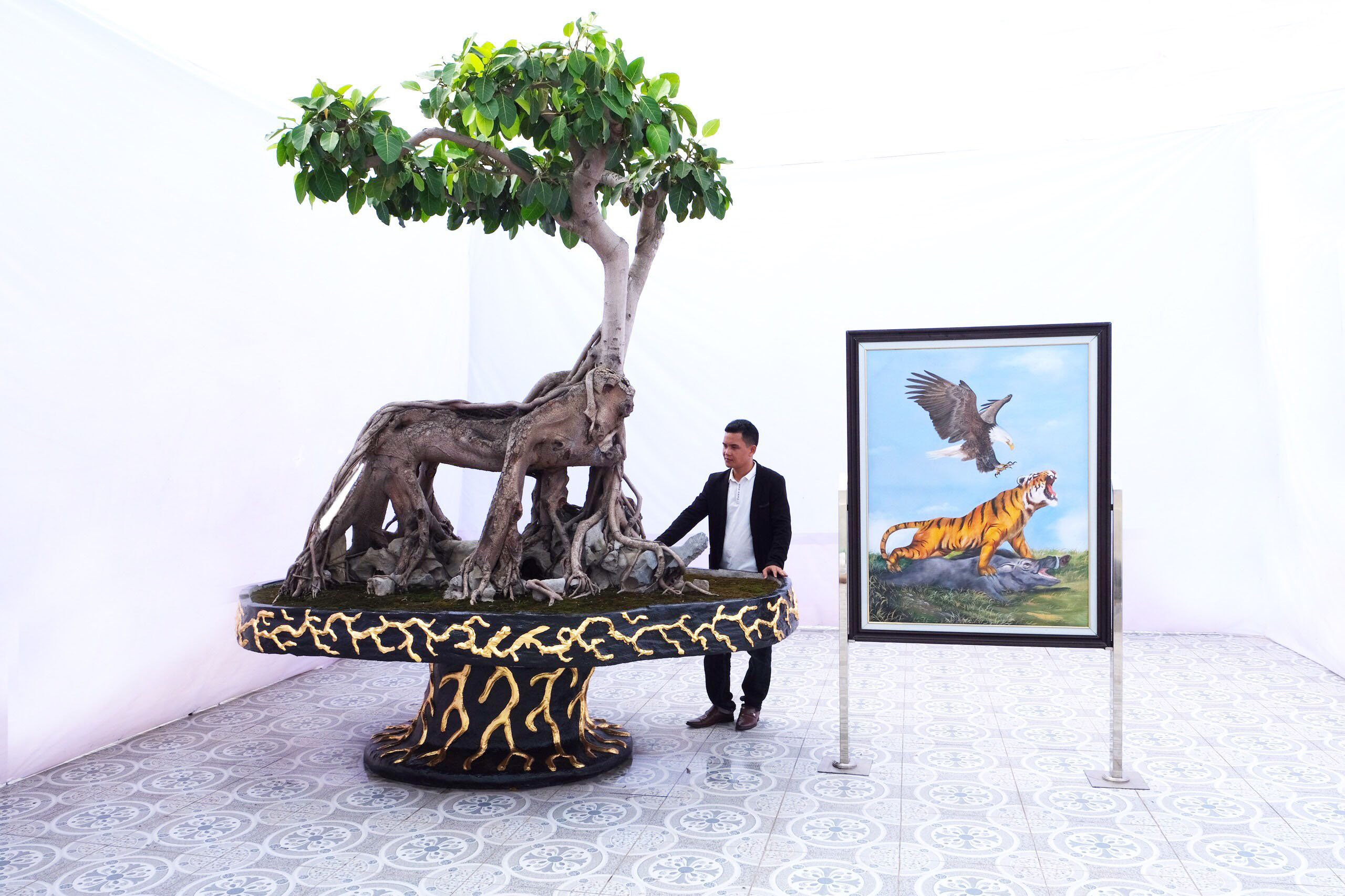 Thân cây hình Mãnh Hổ- chúa tể của muôn loài dưới mặt đất, cũng là biểu tượng của bậc anh hùng hảo hán, bậc quân tử, thể hiện khí chất của người dũng cảm và bản lĩnh.Thân bệ cây sinh trưởng phát triển thành hình Mãnh Hổto lớn và hùng dũng với cơ bắp vạm vỡ cuồn cuộn, bốn nhánh thân của cây biểu hiện bốn chân của mãnh hổ đang ghì bắt con lợn rừng được tạc bằng đá bị đè nằm bên dưới. Bệ rễ của cây đang bám chắc vào đá như những móng vuốt của Mãnh Hổgiữ chặt con mồi.