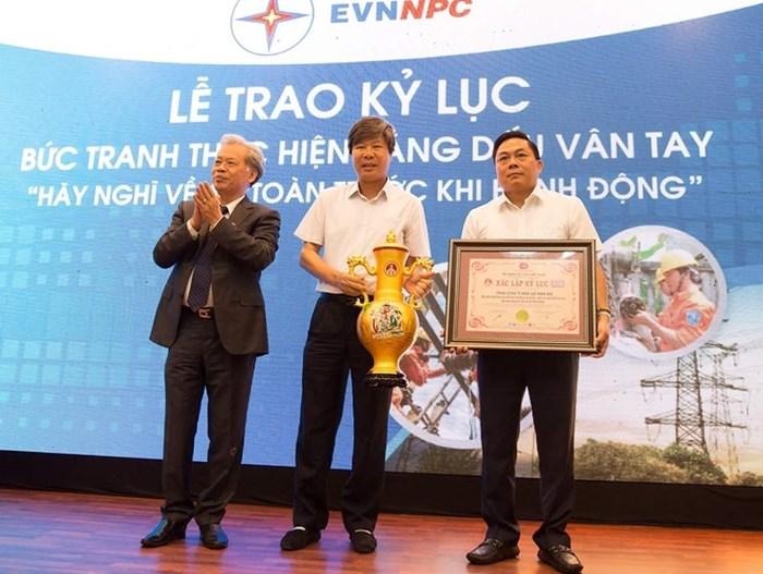 TS Thang Văn Phúc - Chủ tịch TW Hội Kỷ lục gia Việt Nam (ngoài cùng bên trái) trao bằng xác lập Kỷ lục đến ông Lê Minh Tuấn - Phó Tổng giám đốc EVNNPC (ở giữa) và ông Mai Quang Hùng - Trưởng ban an toàn EVNNPC (ngoài cùng bên phải).
